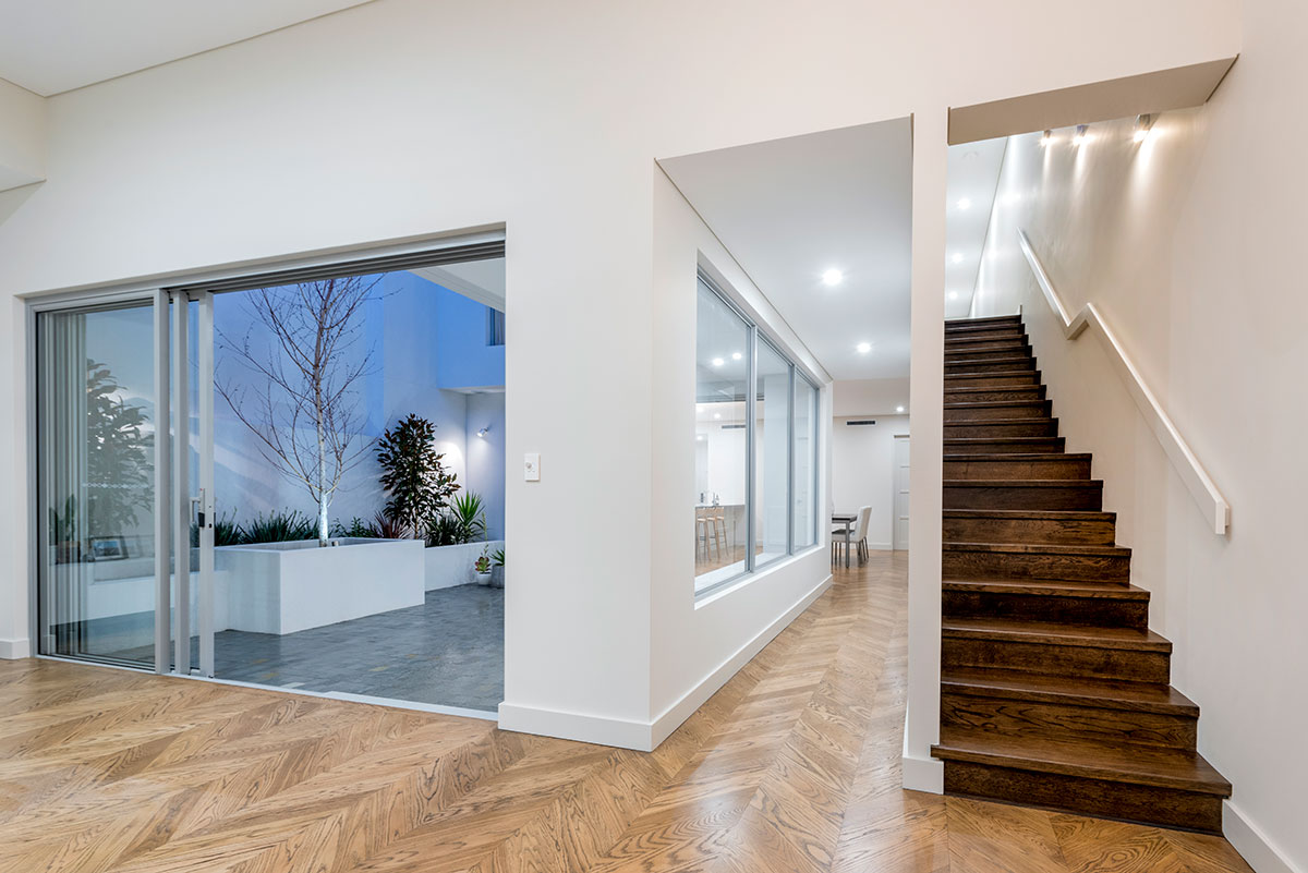 Unique custom wooden staircase leading to second storey dark timber stairs complement the light parquetry solid timber floors in this custom 2 storey home