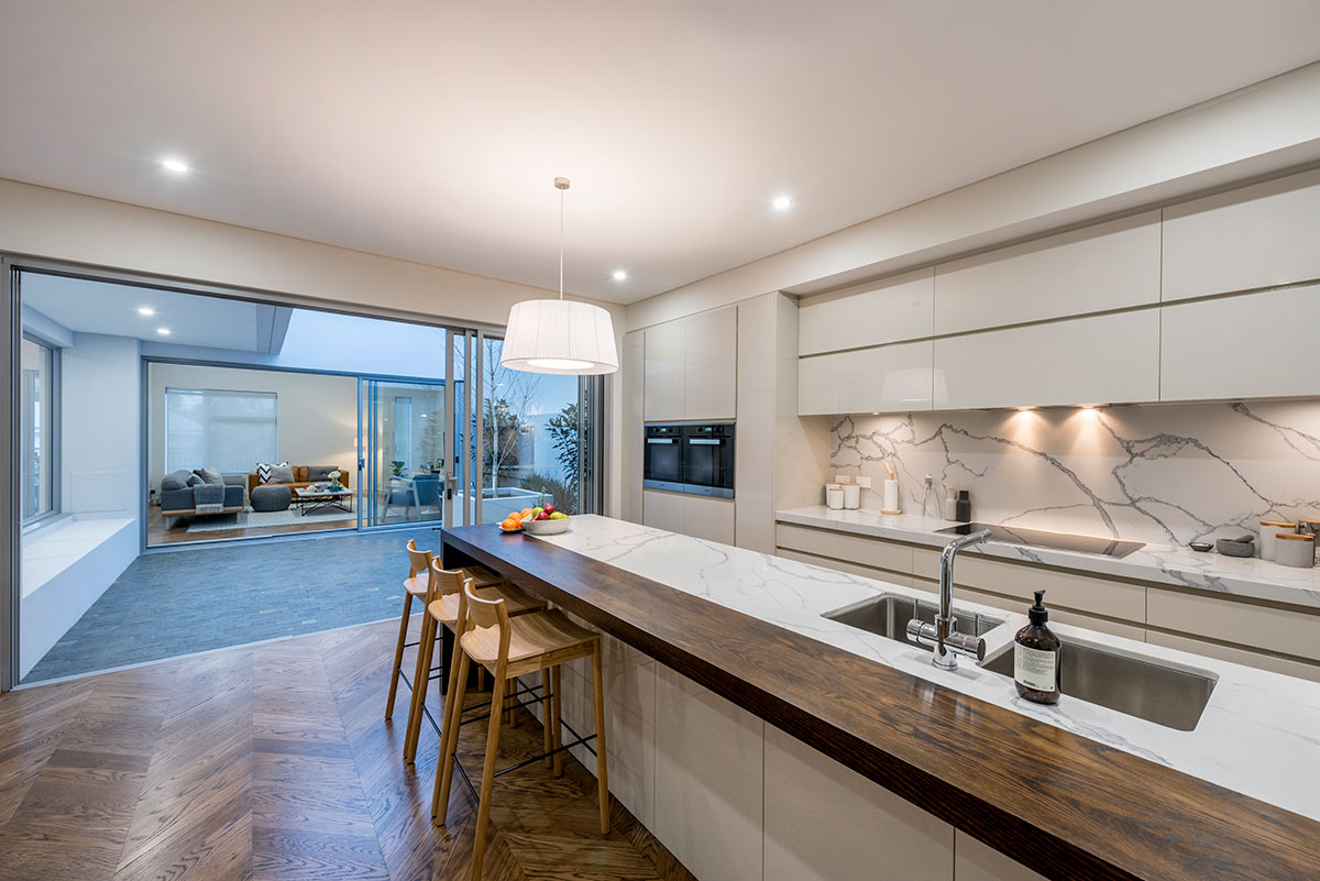 Photo view of luxuriously appointed kitchen and its views of the outdoor entertaing area. Showing Parketry flooring Large frame windows. Located Claremont perth