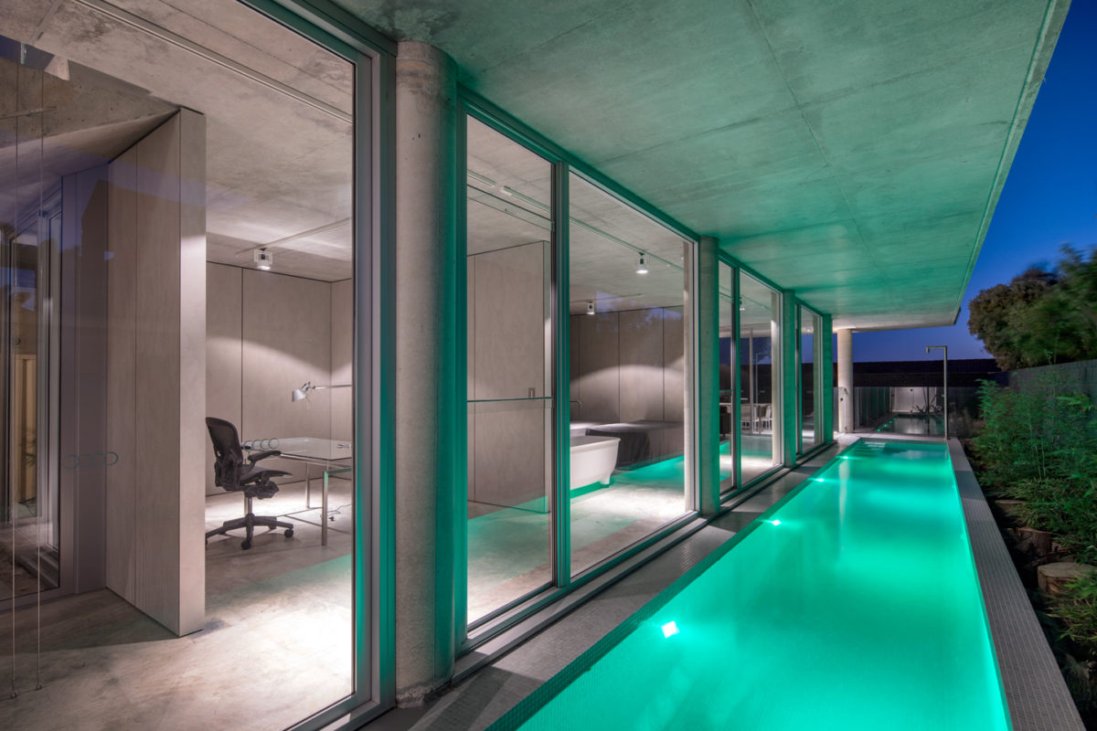 North Beach off form industrial style concrete home lap pool pictured at night view through expansive floor to ceiling doors and windows by Prima Designer Homes