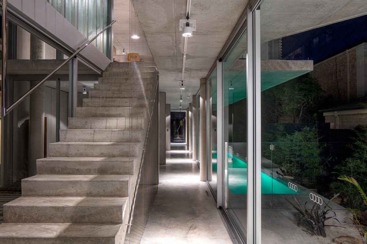 North Beach off form concrete home entry hall at night by Prima Designer Homes